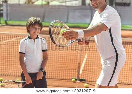 Cheerful father is going to make pitch and his son glancing at it with interested smile. Waist up portrait. Focus on equipment in male hands