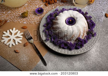 A table with a bunch of cinnamon, almond, physalis, a glass of lemonade, a metal fork, a ring cake sprinkled with sugar powder on a light colorful background.