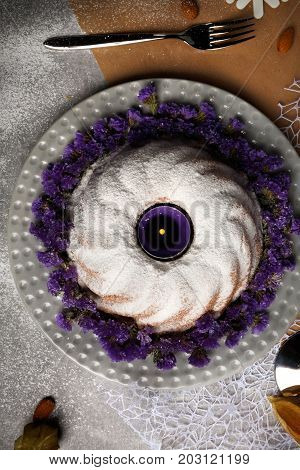 Top view of a table with a bunch of cinnamon, almond, physalis, a glass of lemonade, burning candles, a metal fork, a ring cake sprinkled with sugar powder on a light colorful background.