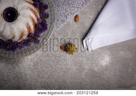 A table with almonds, physalis, a snow-white napkin, a ring cake sprinkled with sugar powder, tasty bakery products for holidays on a light gray background.