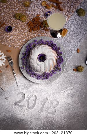 Top view of a glass of lemonade, almond, a ring cake covered with sugar powder, a metal fork, a signature 2018, celebration of New Year on a light gray background.