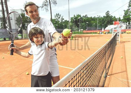Cheerful father is teaching son to make tennis pitch in right way. They standing near grid and looking at ball, child holding with smile. Portrait. Copy space on right side