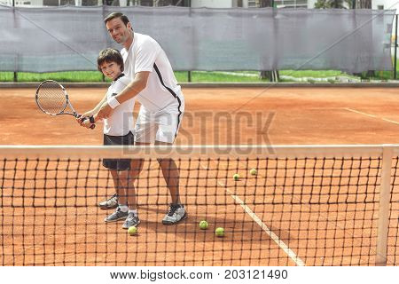 Happy father is teaching his son to beat off pitch. They standing near net on court and looking at camera with bright smile. Full length portrait. Copy space on right side
