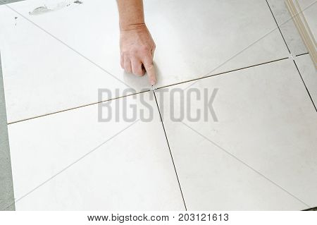 The hand of a tiler is putting a spacer between a ceramic tiles.