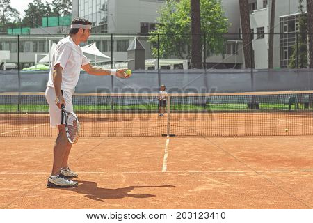 Concentrated father is going to make pitch. He using tennis racket. Son standing at other part of arena. Copy space on right side