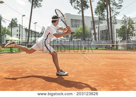 Man is going to beat off pitch of opponent. He holding racket and locating at his part of tennis field. Copy space on right side