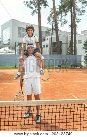 Hilarious son is sitting on father shoulders. They standing on court and looking at camera with smile. Full length portrait. Copy space on right side