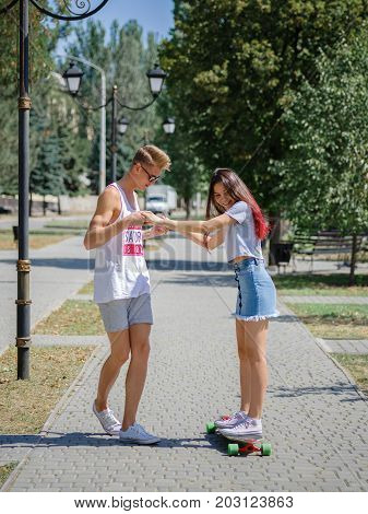 A beautiful couple of teens dating in a park, fellow teaching a girl how to ride on a longboard on a natural blurred background. Dating, love, outdoor, romantic concept.