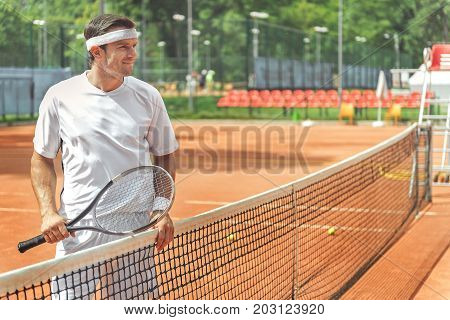 Glad sportsman is holding tennis racket an standing near grid. He looking ahead with expectation. Waist up portrait. Copy space on right side