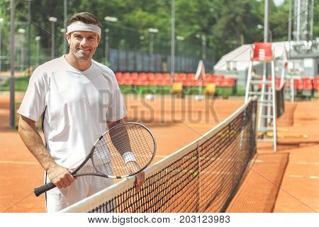 Happy sportsman is standing near grid on court and looking at camera with smile. He holding racket. Waist up portrait. Copy space on right side
