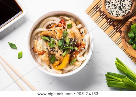 Udon stir-fry noodles with chicken meat vegetables and sesame in white bowl. Traditional asian food. Top view.
