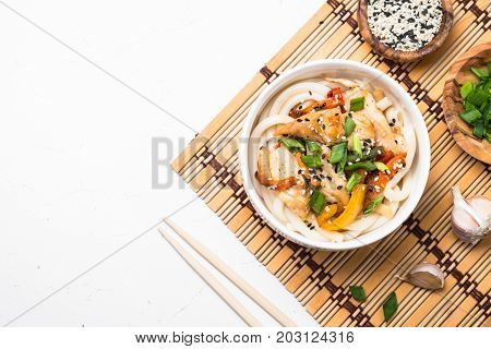 Udon stir-fry noodles with chicken meat vegetables and sesame in white bowl on white table. Traditional asian food. Top view.