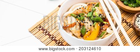 Udon stir-fry noodles with chicken  vegetables and sesame in white bowl. Traditional asian food.