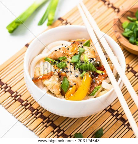 Udon stir-fry noodles with chicken  meat vegetables and sesame in white bowl. Traditional asian food. Square.