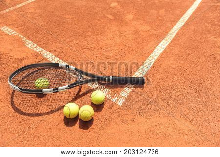 Few small balls locating near professional tennis racket. Things are on white mark at arena. Top view. Copy space on right side