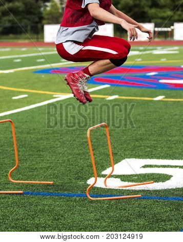 A high school football player jumps over orange hurdles during practice on a green turf field for strength power and agility work.