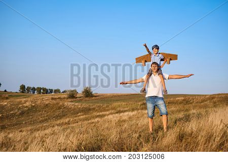 Son on the shoulders of his father in the open air in the field. Father's Day.