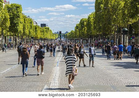 Paris- July 62017: People walking on the famous French boulevard Champs Elysees closed for car traffic. Each first Sunday of the month The Boulevard is closed for car traffic symbolising the fight of parisians against the pollution.