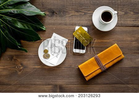 Pay restaurant bill. Bill, bank card, wallet, coins near cup of coffee on dark wooden table top view.