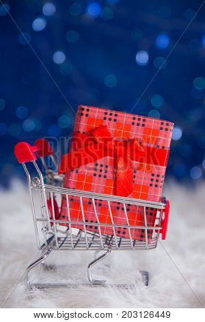 Red Gift Box In Small Supermarket Trolley On Blue Bokeh Background