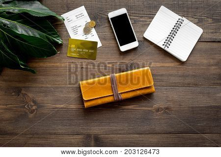 Pay restaurant bill. Bill, bank card, wallet, coins on dark wooden table top view.