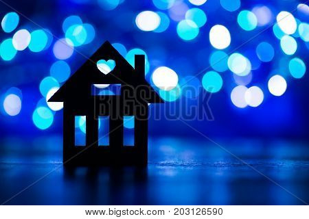 Silhouette Of House With Hole In Form Of Heart On Blue Bokeh Background