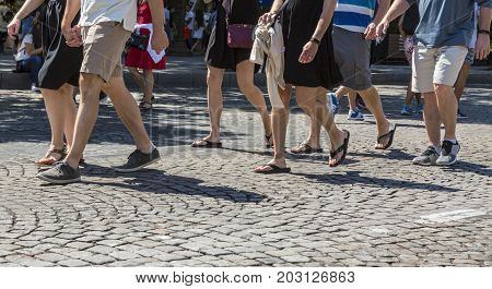 Paris- July 62017: Detail image of the legs of unidentified people walking on the famous Boulevard Champs Elysees closed for car traffic. Each first Sunday of the month The Boulevard is closed for car traffic.