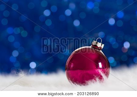 Burgundy Christmas Ball On White Fur With Garland Lights On Blue Bokeh Background