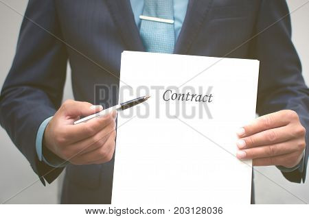 Contract conclusion. Signing of the contract. Business man holding blank document page in front of him and pointing pointing at him with a pen. Credit registration. Dealing.