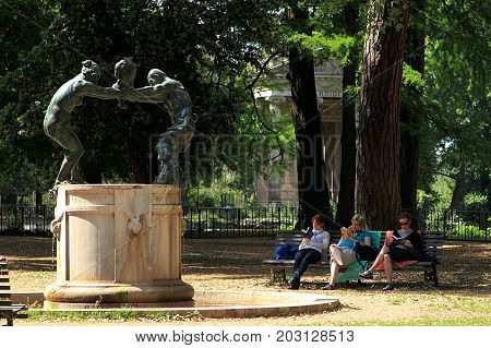 Rome, Italy - May 16, 2012: Fontana della famiglia dei Satiri in Villa Borghese garden with three women reading on the bench nearby.
