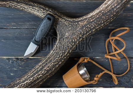 Small Hunting Knife And A Glass In A Leather Case. The Horn Of A Deer.