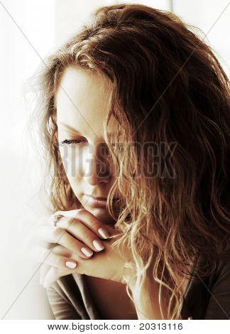 Sad woman against a window.