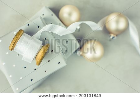 Stacked gift boxes wrapped in silver paper with polka dots pattern. Wooden spool with white curled silk ribbon Christmas baubles on stone marble background. Top view copy space.