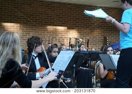 JOLIET, ILLINOIS / UNITED STATES - JUNE 1, 2017: The Metropolitan Youth Symphony Orchestra (MYSO) prepares to perform for an outdoor Concert on the Hill in the Billie Limacher Bicentennial Park.