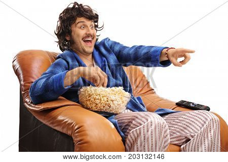 Retro guy seated in an armchair watching television and laughing isolated on white background