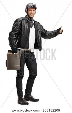 Full length portrait of a biker holding a gas container and hitchhiking isolated on white background
