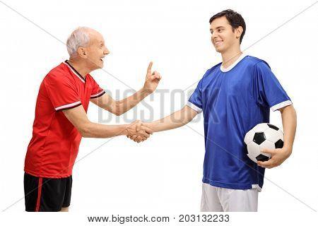 Old soccer player shaking hands with a young player and advising him isolated on white background