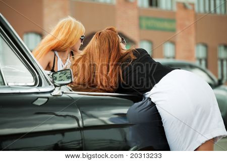 Two young women with a retro car.