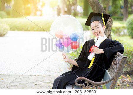 Portrait Of Happy Young Female Graduates In Academic Dress And Square Academic Cap Holding Word Quot