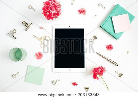 Flat lay fashion office desk. Female workspace with tablet red flowers accessories mint diary on white background. Top view feminine background.