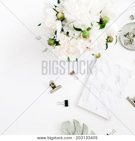 Flat lay home office desk. Woman workspace with white peony flowers bouquet accessories marble diary on white background. Top view feminine background.