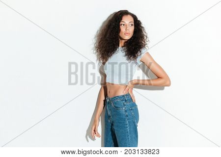 Side view of attractive curly woman posing in studio over white background