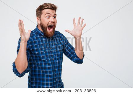 Screaming shocked bearded man in casual looking at copy space and screaming isolated over white