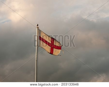 england flag flying with cloudy dramatic skies during sunset; Essex; England; UK