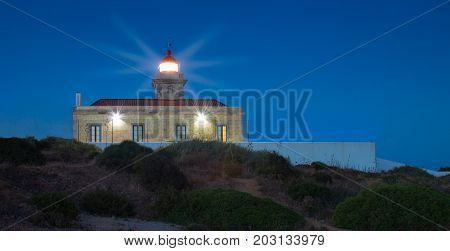 The lighthouse in Lagos Algarve Portugal during night. Lights are shining for the maritime safety in Atlantic ocean. Blue hour photo of the lighthouse.