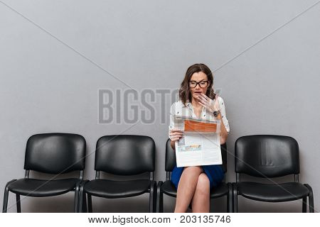 Surprised business woman in eyeglasses sitting on chairs and reading newspaper