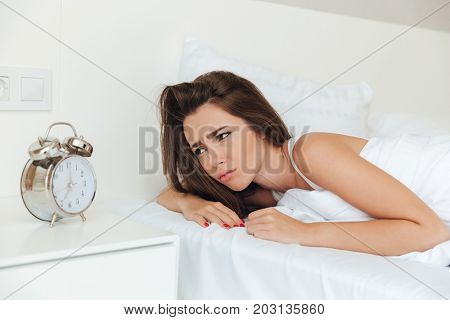 Upset sleepy woman laying in bed in the morning and looking at ringing alarm clock