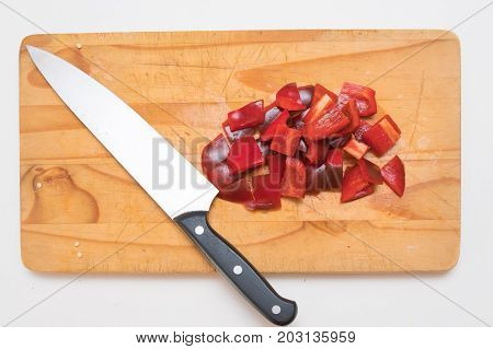chopped red bell peppers on a wooden chopping board with a steel knife