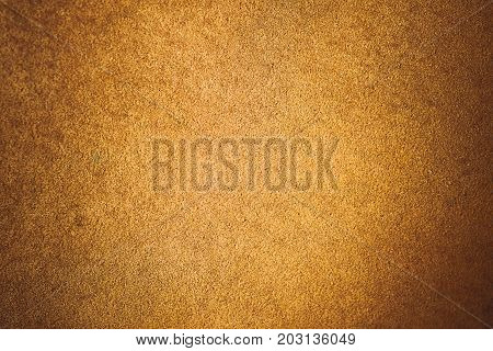 Old aged suede leather background. Coarse texture gradient yellow brown beige vivid colors. Vignette toned.