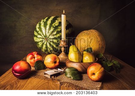 Fruit still life with pears nectarines melon watermelon and candle in a carved candle holder